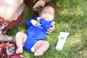 mom outside with baby on grass after apply proven mosquito repellent