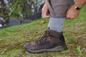 man protecting himself from ticks by using tick repellent, tucking his pant legs into his wool socks, and wearing hiking boots in the woods